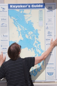Kayaker searches map of Puget Sound, WA. (Hadi Dadashian photo)